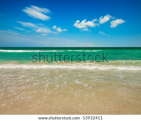 Empty tropical ocean beach with set of clouds over water