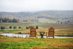Empty two romantic wooden chairs in autumn fall foliage season countryside at Charlottesville winery vineyard in blue ridge mountains of Virginia with cloudy sky day