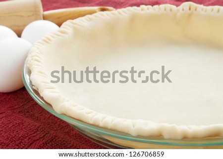 empty uncooked pie crust with raw eggs and a wooden rolling pin in the background. Selective focus on the pie crust.