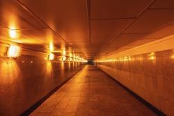 Empty underground passage illuminated with yellow light