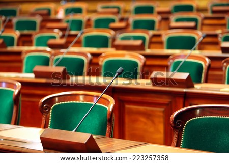 Shutterstock Empty vintage congress hall with seats and microphones.