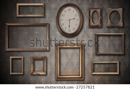 empty vintage frames and watch against an dirty wall - stock photo