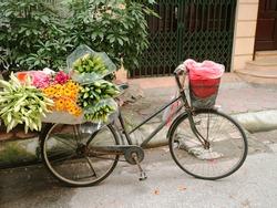Empty Vintage Vietnamese Bicycle load Flower Multicolor Selling on Street rain coat in basket