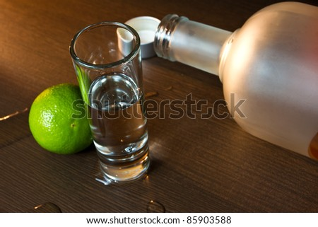 Empty vodka bottle with lime on the wet table