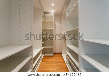Empty walk-in closet with white shelves and parquet. Nobody inside