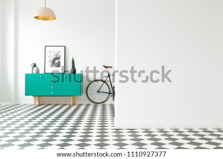 Empty wall and turquoise cabinet with decorations standing next to a bike in a hallway interior with checkered floor. Place for your poster or furniture #1110927377