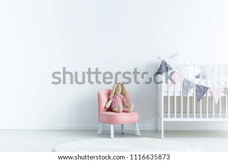 Empty wall next a to chair with a rabbit and crib with triangles on the rope in a baby room interior. Place your product #1116635873