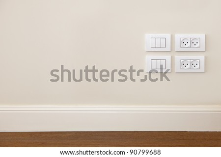 Empty wall with wooden floor. On the wall power outlet and  light switch