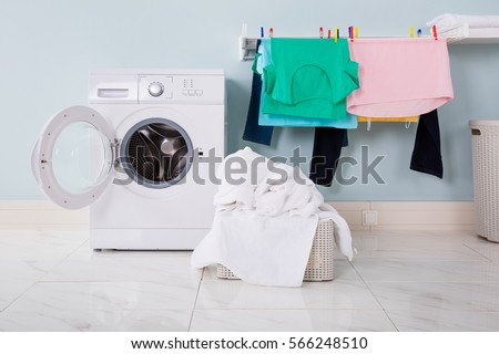 Empty Washing Machine With Pile Of Dirty Cloth In The Basket At Laundry Room #566248510