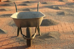 empty wheelbarrow on the surface of red bricks and heaps of gravel. construction topic