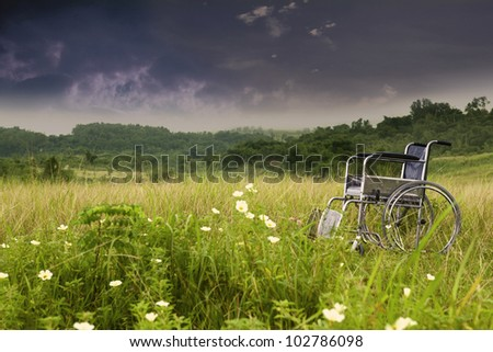 Empty wheelchair in cloudy day symbolizing sadness and loneliness