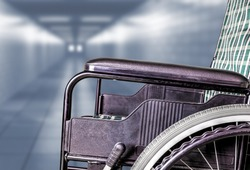Empty wheelchair in hallway of hospital or retirement nursing care home with copy space. Concept of sickness, loneliness, neglect, isolation due to pandemics, outbreaks, epidemics, illness, lockdowns.