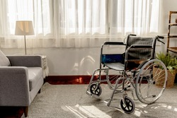 Empty wheelchair in the livingroom. Lonely and healthcare concept.