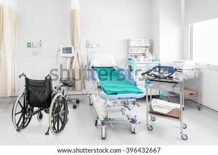 Empty wheelchair parked in hospital room with beds and comfortable medical equipped in a modern hospital
