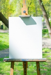 Empty white artist's canvas on the easel. Creative mockup background. Vertical composition.