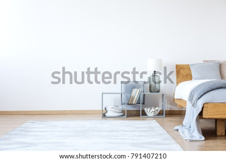 Empty white bedroom interior with bed with woolen blanket, shelves and snowy white carpet Foto d'archivio ©