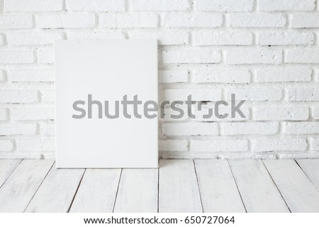 Empty white canvas frame on a wooden table #650727064