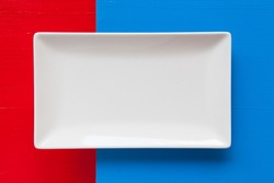 Empty white ceramic dish on over blue and red background, rectangle dish
