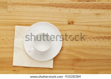 empty white china coffee cup and napkin on pine wood table, top view