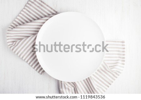 Empty white circle plate on wooden table with linen napkin. Overhead view.