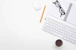 Empty white desk office with glasses pencil coffee and keyboard