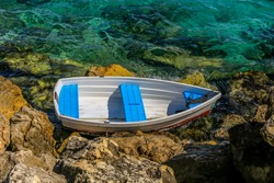Empty white dingy sits washed up on rocks in clear ocean