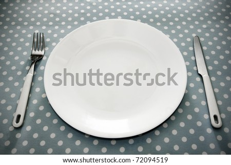 Empty white dinner plate with utensils on fun grey polka dot tablecloth.