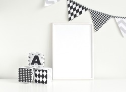 Empty white frame mockup for artwork, painting, posters or photo, monochrome nusery interior with blank frame, flags bunting and soft baby blocks.