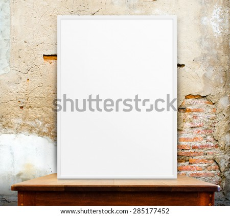 Empty white frame on wooden table at grunge concrete wall in background,Mock up for adding your design,