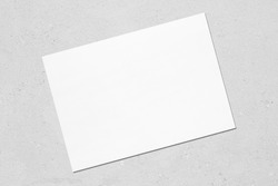 Empty white horizontal rectangle poster mockup with soft shadow lying diagonally on neutral light grey concrete background. Flat lay, top view