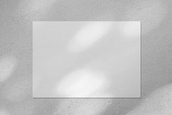 Empty white horizontal rectangle poster or business card mockup with diagonal dappled light spots on gray concrete wall. Flat lay, top view. For advertising, brand design, stationery presentation.
