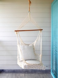 Empty white knitting rope swing hanging from ceiling on white wood background in room terrace in the resort vertical style. Vintage white handcraft hammock decoration on balcony.