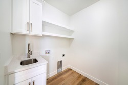 Empty white laundry room with top storage, laundry connections and dryer vent on the wall. There is a single vanity deep stainless sink beside laundry water outlet on the wall with electrical plug.
