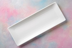Empty white long rectangular plate on a colored background.