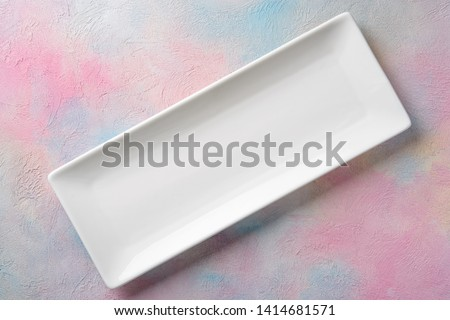 Photo of  Empty white long rectangular plate on a colored background.