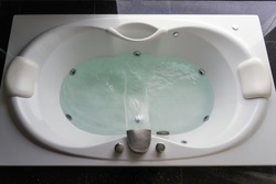 Empty white massaging jetted bathtub with turquoise water on black polished stone floor.