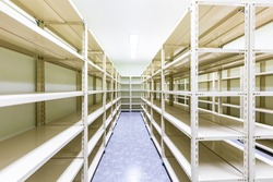 Empty white metal shelves in storage room