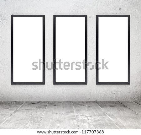 Empty white old interior room with painted concrete wall and empty black wood frames and wooden plank floor
