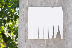 Empty white paper posted on a cement street post and marked with your own message. Blank advertisement with cut slips