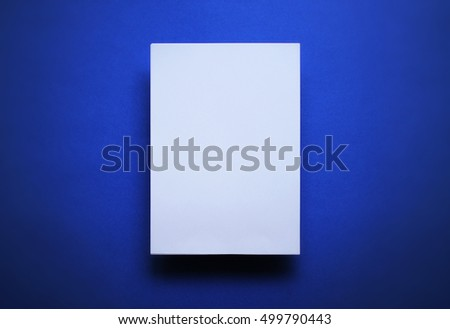 Empty white paper sheet isolated on blue background #499790443