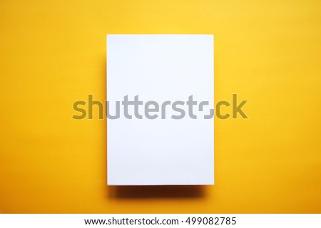 Empty white paper sheet isolated on yellow background