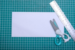 Empty white paper with scissors and ruler on cutting mat. Empty white paper for copy space