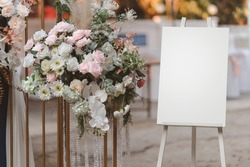 Empty white photo display board on stand for wedding arch.