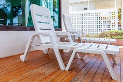 Empty white plastic sun loungers in front of the rooms at the seaside resort