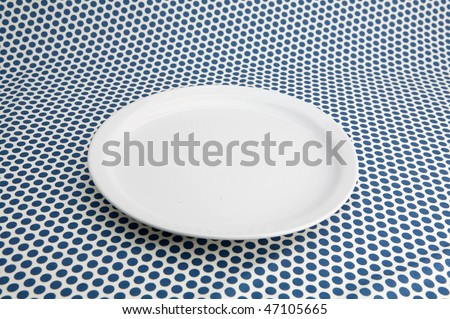 Empty white plat on table caver by blue tablecloth