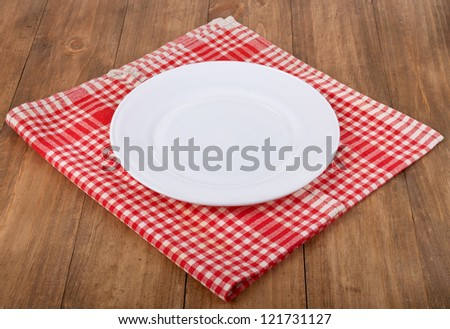 Empty white plate at classic checkered tablecloth on wooden table