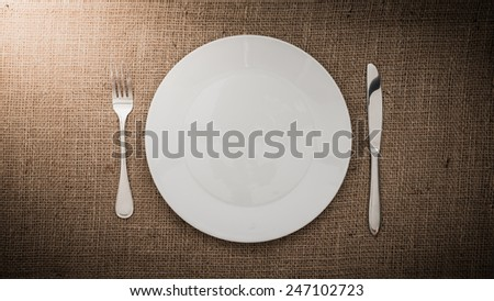 Empty white plate   fork, knife on sackcloth background
