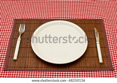 Empty white plate on a kitchen table.