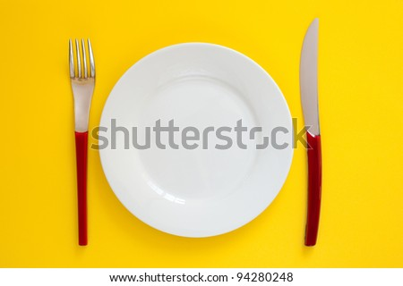 Empty white plate on a yellow background with red handle fork and knife. Simple, clean and bright top view shot with room for copy.