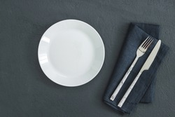 Empty white plate on black table and napkin. Food background for menu, recipe. Table setting. Flatlay, top view. Mockup for restaurant dish